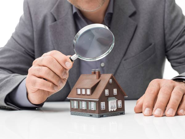 man in suit holding magnifying glass over model home